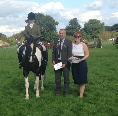 Mrs H M Bailey and her horse Badger, receiving their engraved silver salver and rosette from judge Steve Arnold and Vicki Gumbley from Bill Bird Shoes.